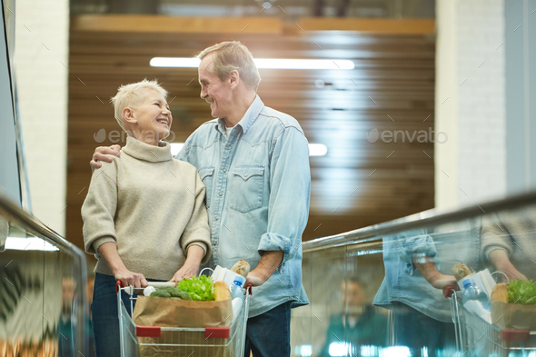 Smiling Senior Couple Shopping in Mall - Stock Photo - Images