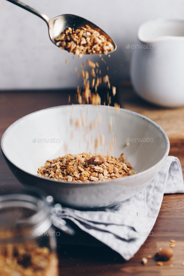 Hand sprinkles baked granola in a ceramic bowl - Stock Photo - Images