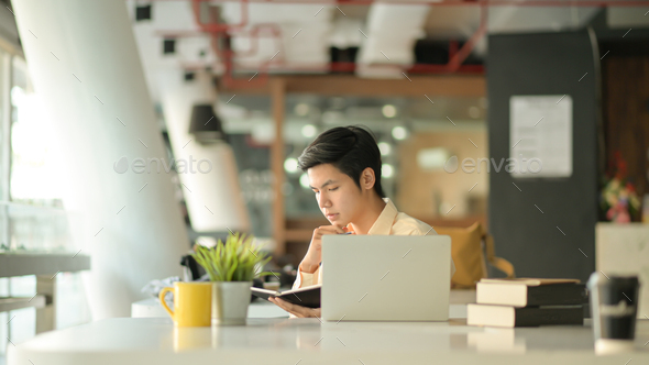 Young businessmen are reading work records in modern offices and office equipment. - Stock Photo - Images