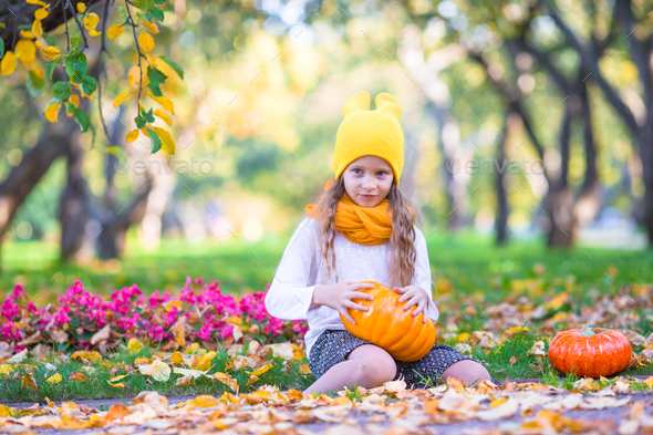 Adorable little girl with pumpkin outdoors at beautiful autumn day. Trick or treat - Stock Photo - Images