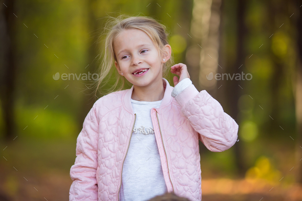 Adorable little girl outdoors at beautiful autumn day - Stock Photo - Images