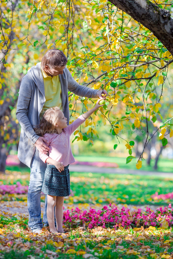 Father and little girl having fun on beautiful autumn day - Stock Photo - Images