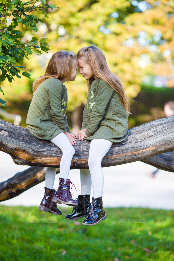 Little adorable girls outdoors at warm sunny autumn day - Stock Photo - Images