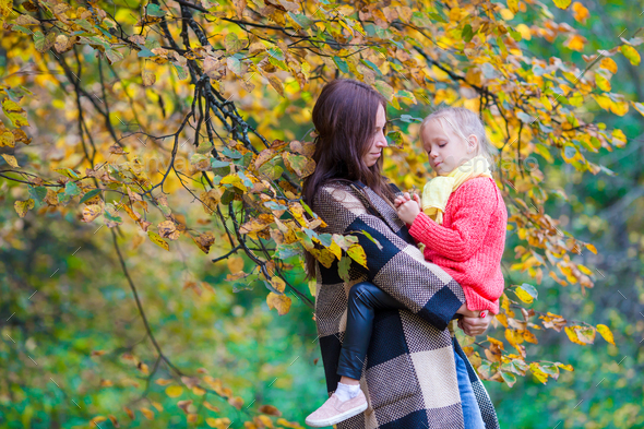 Adorable little girl with mother in autumn park outdoors - Stock Photo - Images