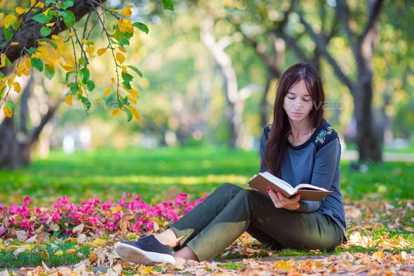 Young woman reading book in beautiful autumn day - Stock Photo - Images