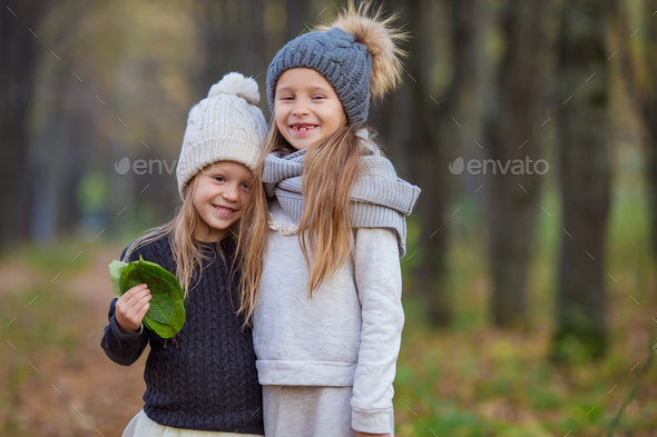 Little adorable girls outdoors at warm autumn day - Stock Photo - Images