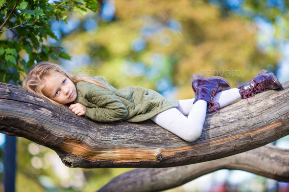 Adorable little girl outdoors at beautiful warm day in autumn park - Stock Photo - Images