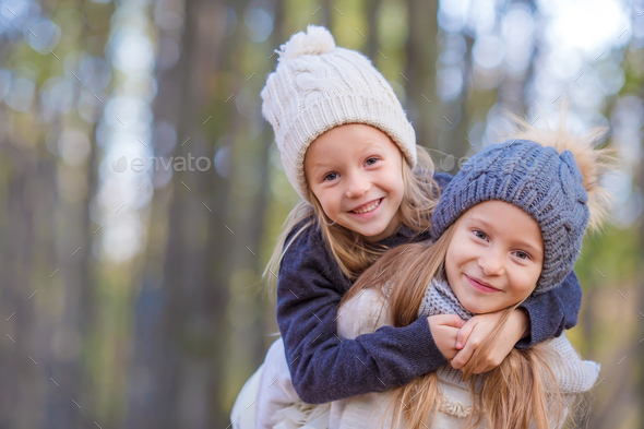 Little adorable girls at warm sunny autumn day outdoors - Stock Photo - Images
