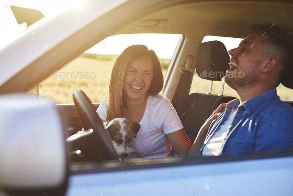 Joyful scene of young couple and dog during road trip - Stock Photo - Images
