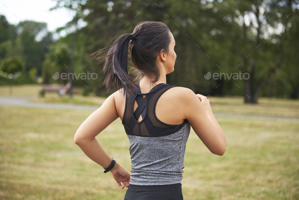 Rear view of young woman running in the park - Stock Photo - Images