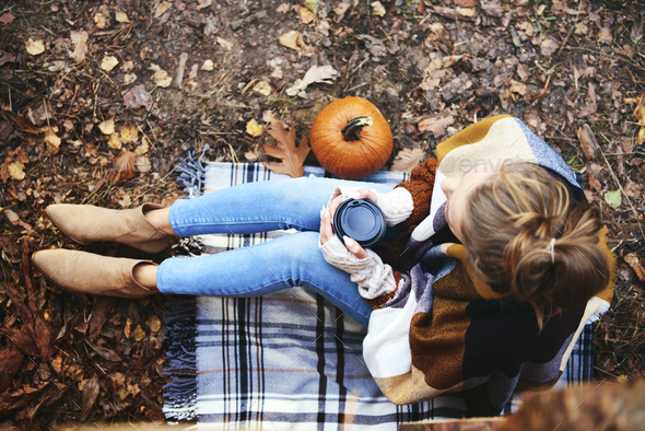 High angle view of woman with coffee relaxing in autumn forest - Stock Photo - Images