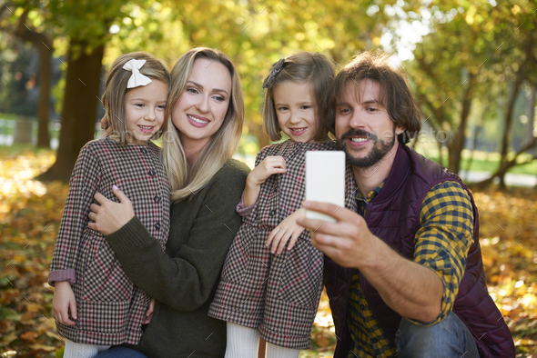 Family with two children making a selfie in autumn woods - Stock Photo - Images