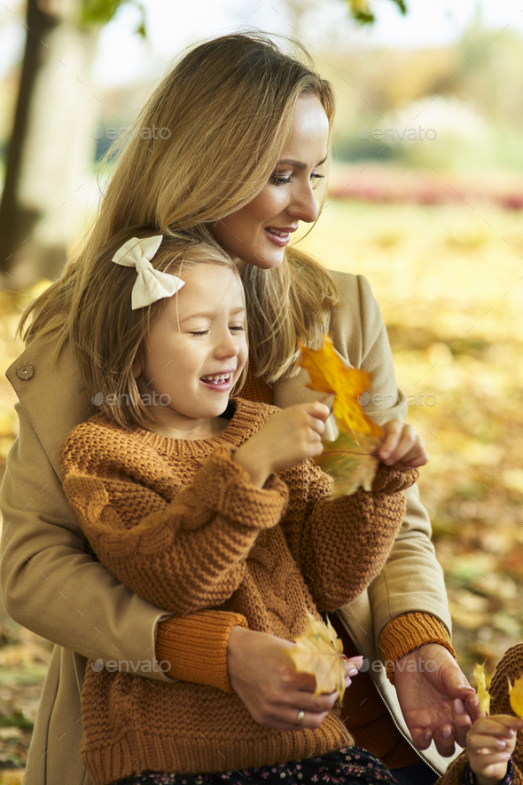 Mother and daughter picking leafs on the fall season - Stock Photo - Images