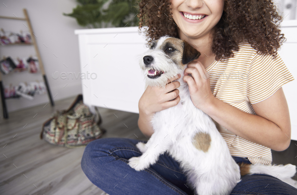 Young woman stroking her dog - Stock Photo - Images