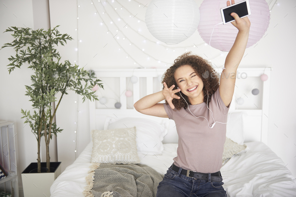 Portrait of happy teenage girl listening to music and dancing - Stock Photo - Images