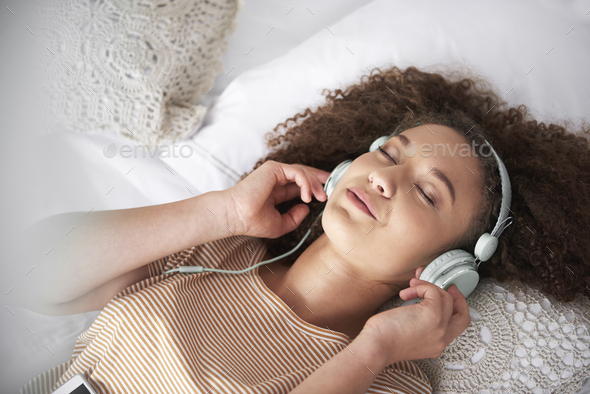 Teenage girl listening to music and lying on the bed - Stock Photo - Images