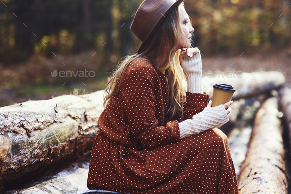Side view of beautiful woman drinking coffee in autumn forest - Stock Photo - Images