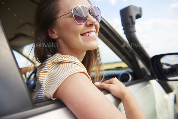Smiling young woman looking at view during road trip - Stock Photo - Images