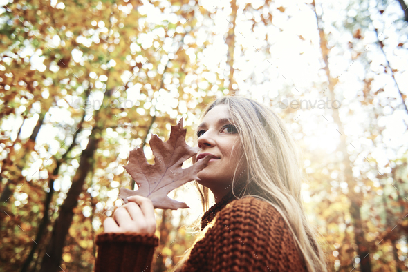 Beautiful  woman holding autumnal leaf - Stock Photo - Images