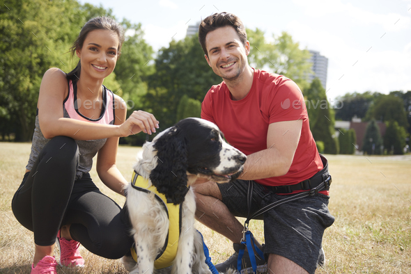 Smiling couple and dog after workout on the fresh air - Stock Photo - Images