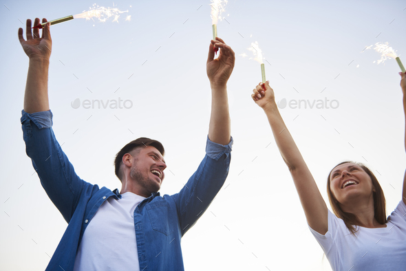 Young couple having fun with some sparklers - Stock Photo - Images