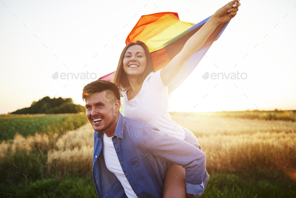 Young woman waving rainbow flag on men's arms - Stock Photo - Images