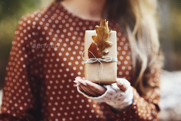 Woman's hand holding gift wit autumnal leaf - Stock Photo - Images