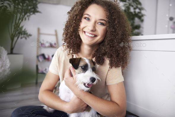 Portrait of smiling teenage girl with her dog - Stock Photo - Images