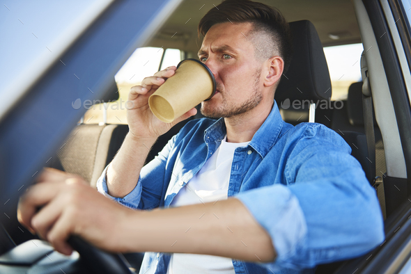 Stressed man driving a car and drinking coffee in a rush - Stock Photo - Images