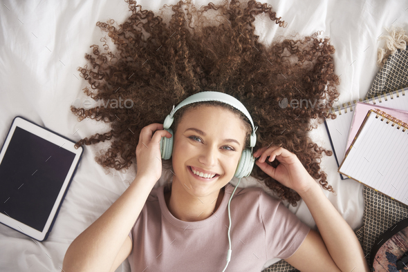 Beautiful teenage girl listening to music in her bed - Stock Photo - Images