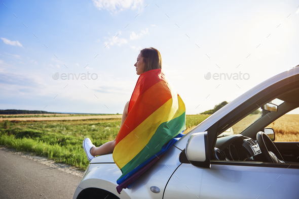 Young woman with rainbow flag enjoying the view - Stock Photo - Images
