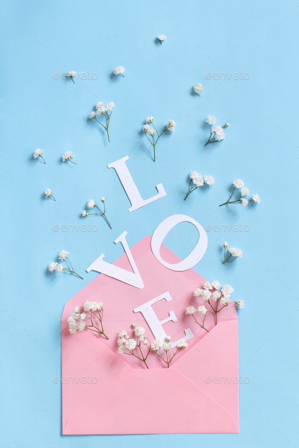 Flowers, envelope and word LOVE on a light blue background - Stock Photo - Images