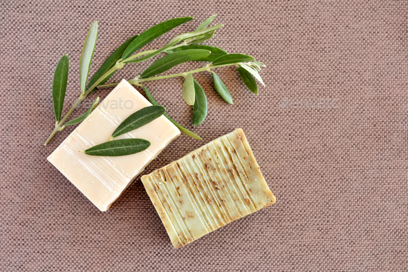 Handmade soap bars and olive branches on fabric background. Top view - Stock Photo - Images