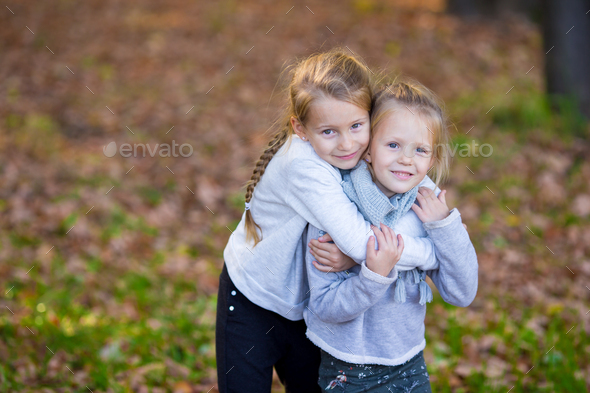 Little adorable sisters at warm sunny autumn day outdoors - Stock Photo - Images