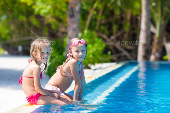 Adorable little girls in outdoor swimming pool on vacation - Stock Photo - Images