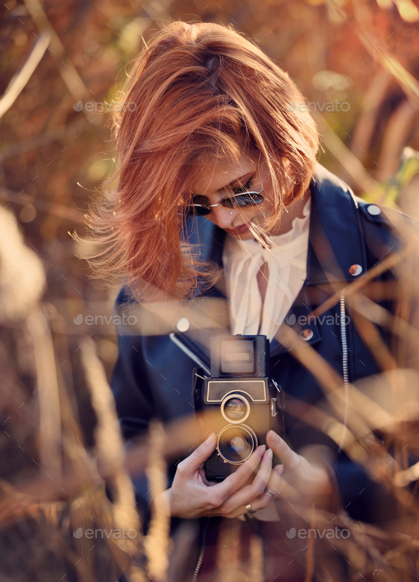 Beautiful young redhaired woman shoots on a retro camera - Stock Photo - Images