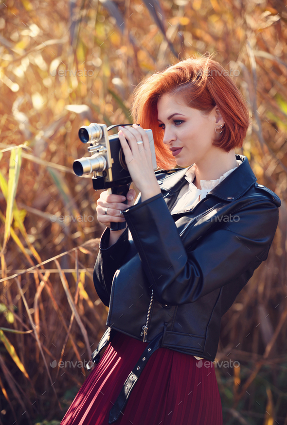 Beautiful young redhaired woman holds a video camera - Stock Photo - Images