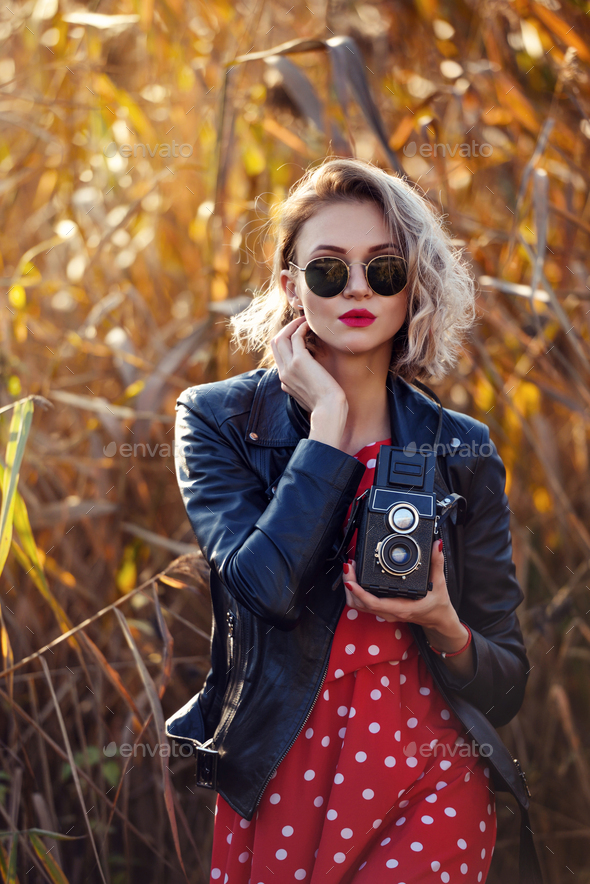 Beautiful young blonde woman in glasses with the retro camera outdoors - Stock Photo - Images