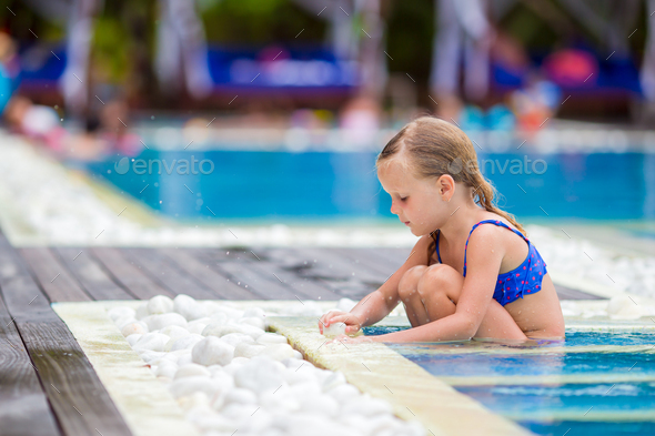 Little happy adorable girl in outdoor swimming pool - Stock Photo - Images