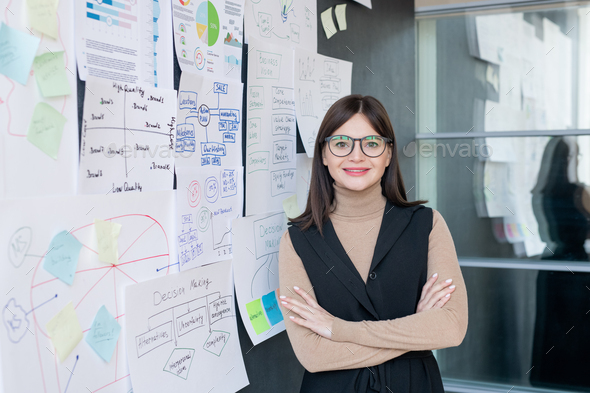 Smiling economist in smart casual and eyeglasses analyzing financial information - Stock Photo - Images