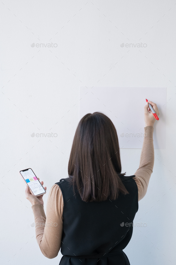 Young businesswoman or student with smartphone going to write on whiteboard - Stock Photo - Images