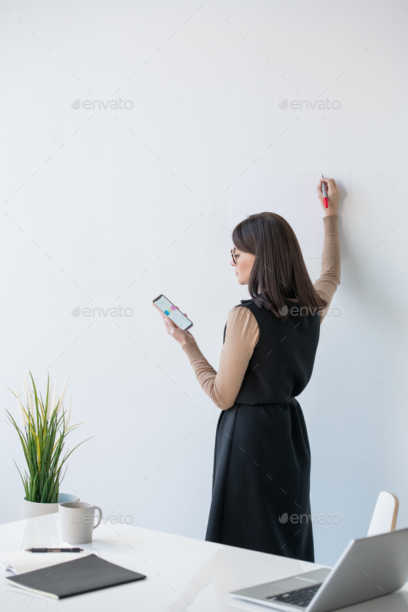 Young elegant coach looking at smartphone screen and going to make presentation - Stock Photo - Images