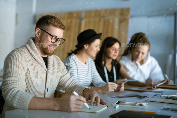 Creative fashion designer drawing sketch in copybook on background of colleagues - Stock Photo - Images