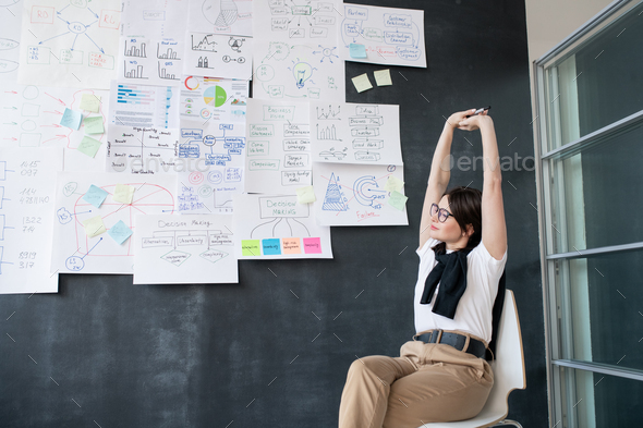 Young tired businesswoman stretching arms while sitting on chair by blackboard - Stock Photo - Images