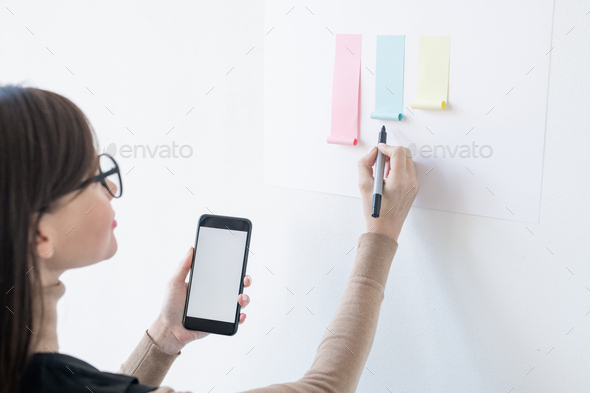 Young female broker with smartphone and highlighter looking at paper chart - Stock Photo - Images