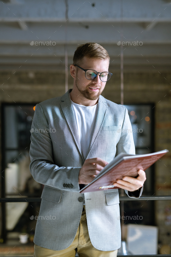 Young confident designer in formalwear looking at cover of fashion magazine - Stock Photo - Images