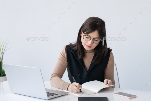 Young elegant teacher or businesswoman making working notes in copybook - Stock Photo - Images