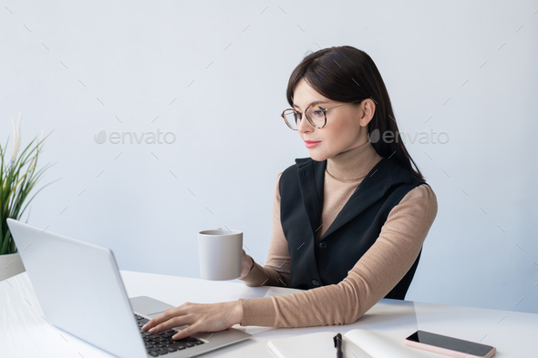 Young serious businesswoman with mug analyzing online financial data - Stock Photo - Images