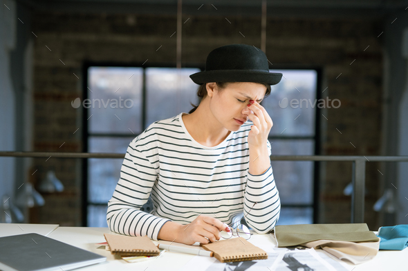 Tired young female designer in hat and striped pullover trying to concentrate - Stock Photo - Images