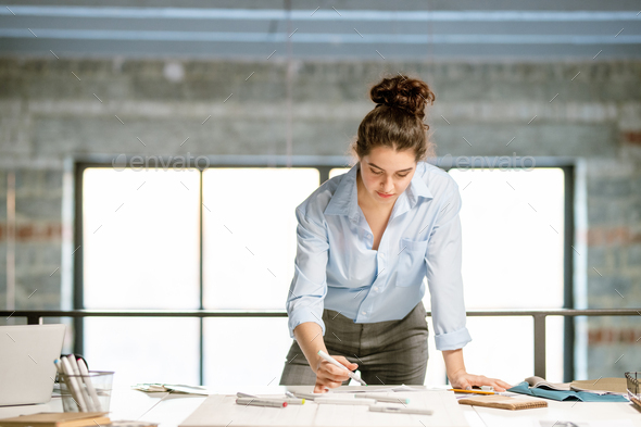 Young serious female designer bending over fashion sketches on desk - Stock Photo - Images